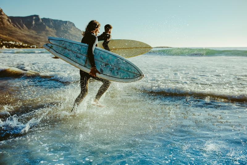 Aan jonge surfers die voor water het surfen gaan stock afbeelding