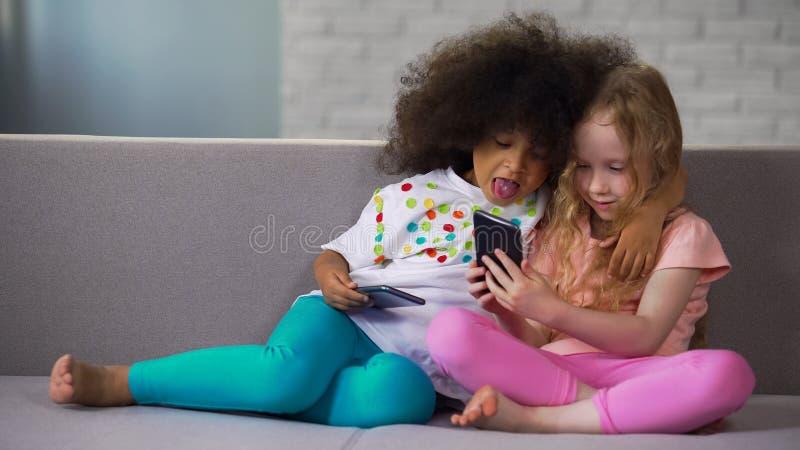Aanbiddelijk Afrikaans Amerikaans meisje die uit haar tong het spelen met vriend zetten selfie stock afbeelding