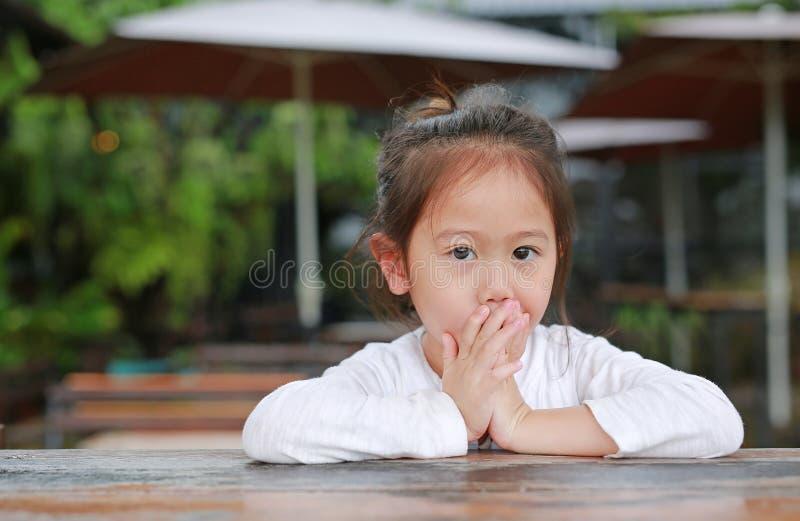 Aanbiddelijk behandelt weinig Aziatisch kindmeisje met handen haar mond liggend op de houten lijst met het kijken camera stock fotografie