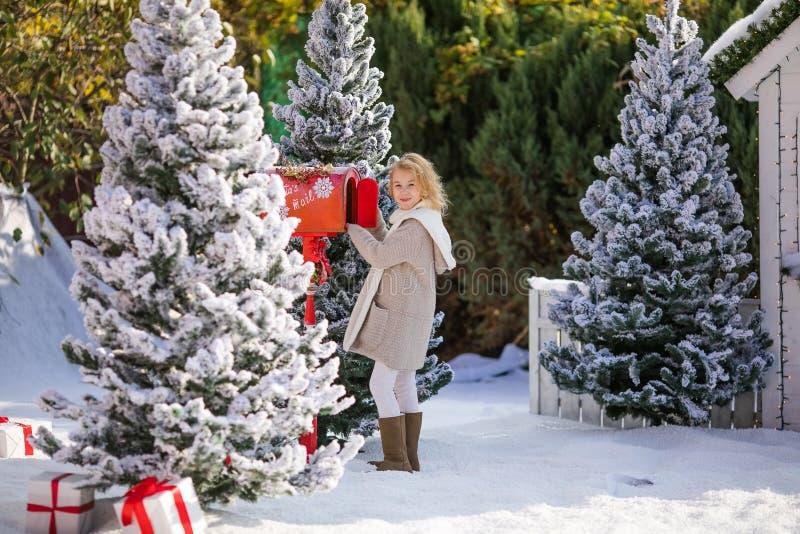 Aanbiddelijk blondemeisje die haar brief naar Kerstman, Kerstmistijd verzenden stock afbeelding