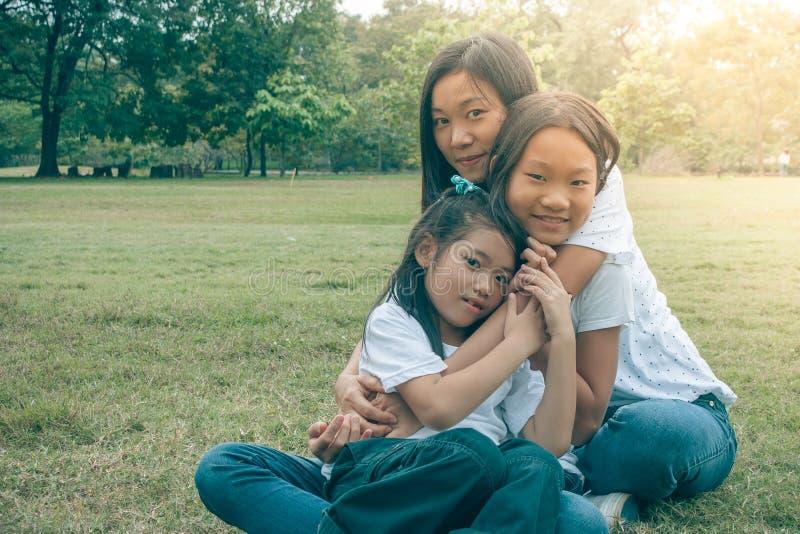 Aanbiddelijk Concept: Vrouw en kind die en het glimlachen geluk in het park koesteren voelen stock afbeelding