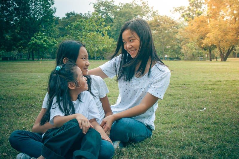 Aanbiddelijk Concept: Vrouw en kind die en het glimlachen geluk in het park koesteren voelen stock foto's