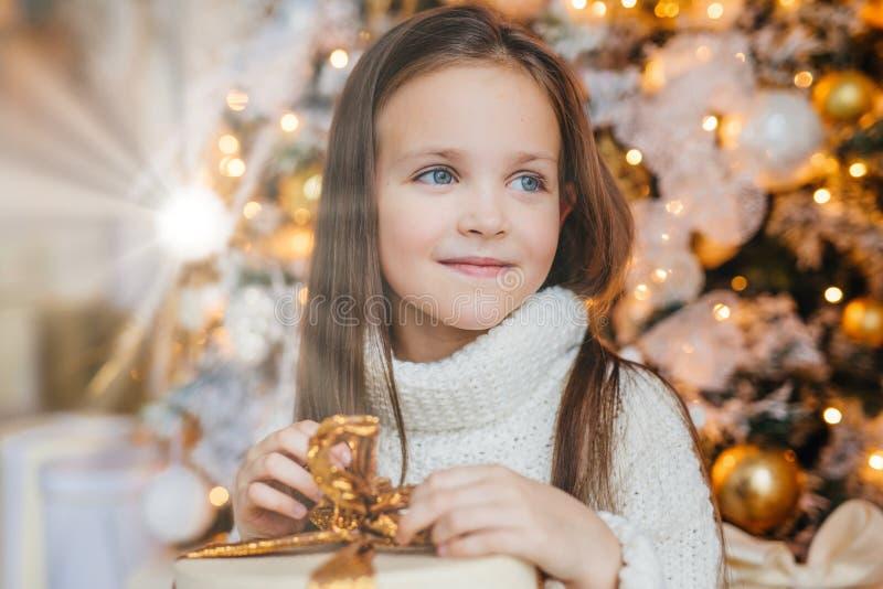 Aanbiddelijk draagt weinig vrouwelijk kind met warme blauwe ogen, lang donker haar, gebreide warme witte sweater, houdt huidige t stock foto
