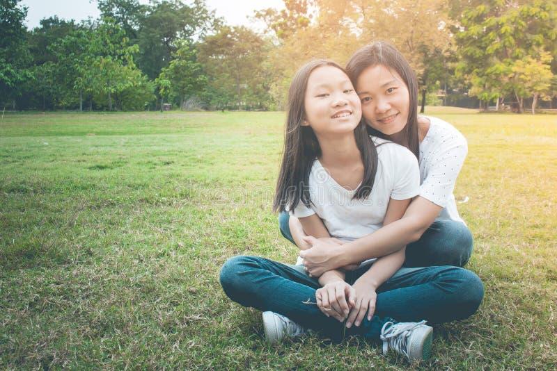 Aanbiddelijk en Familieconcept: Vrouw en kind de zitting ontspant op groen gras Zij die en het glimlachen geluk koesteren voelen stock afbeelding