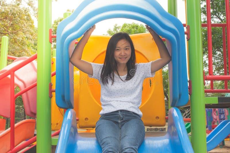 Aanbiddelijk en Vakantieconcept: Spruit het Aziatische vrouw grappig voelen en geluk op speelplaats stock foto