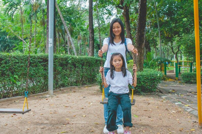 Aanbiddelijk en Vakantieconcept: Vrouw en kind voelen grappig en geluk op een schommeling bij speelplaats stock foto
