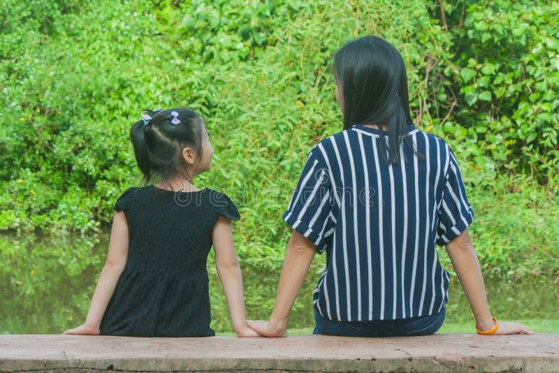 Aanbiddelijk Familieconcept: De Aziatische en vrouw en kinderen die ontspannen op concrete lange bank glimlachen de zitten stock afbeelding