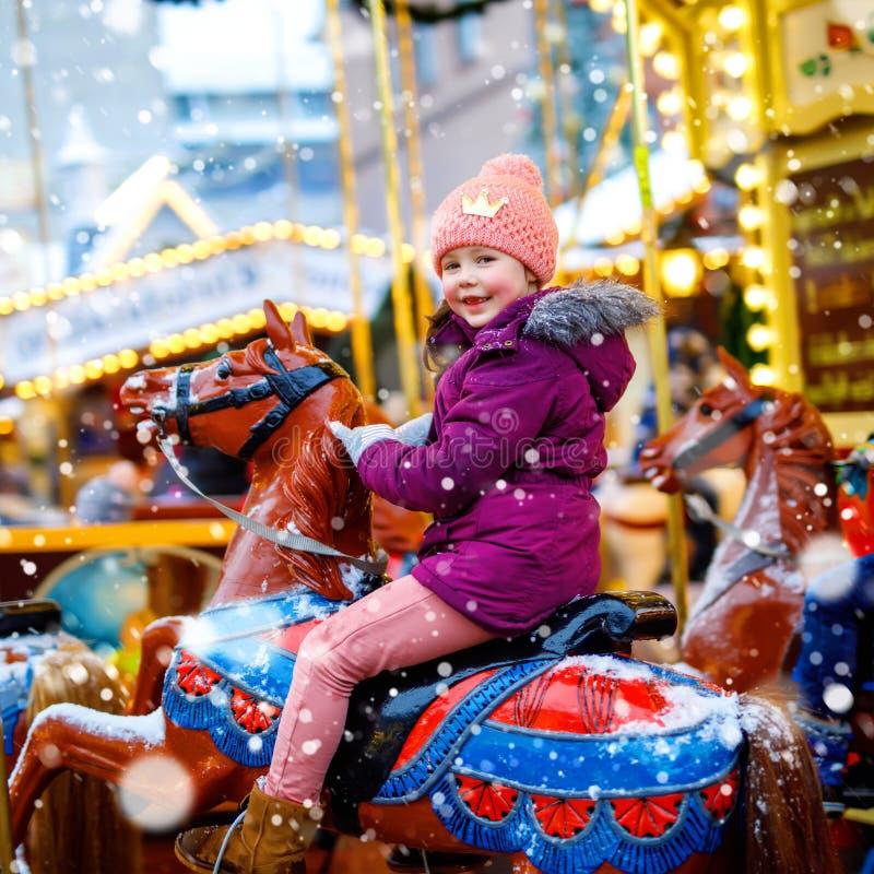 Aanbiddelijk gaat weinig jong geitjemeisje die op vrolijk berijden om carrouselpaard bij Kerstmis funfair of markt, in openlucht  royalty-vrije stock afbeeldingen