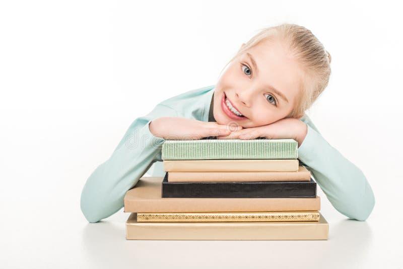 aanbiddelijk gelukkig schoolmeisje die met boeken bij camera glimlachen stock afbeelding