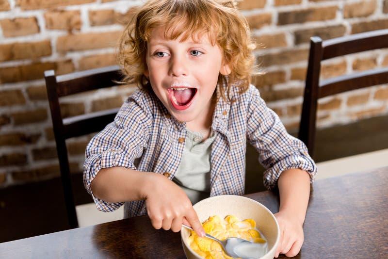 aanbiddelijk gelukkig weinig jongen die cornflakes eten stock afbeelding