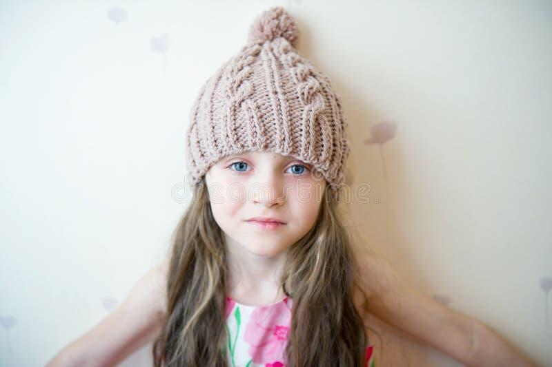 Aanbiddelijk glimlachend kindmeisje in beige gebreide hoed stock foto