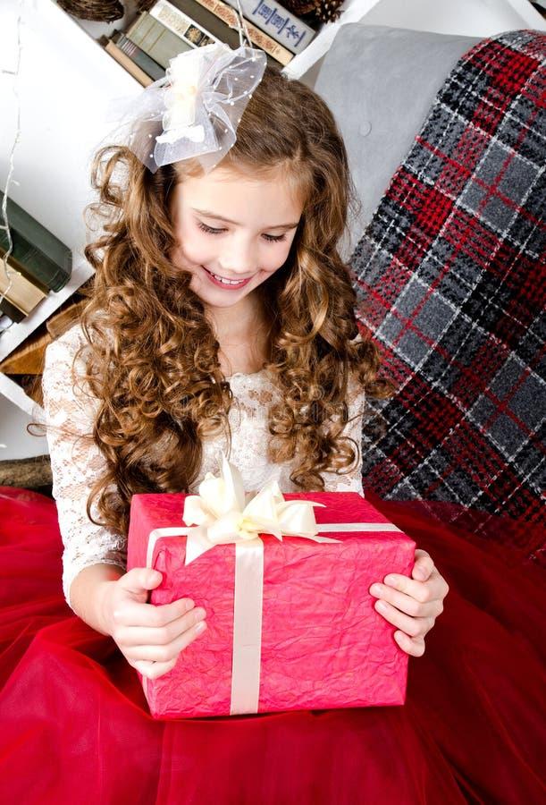 Aanbiddelijk glimlachend meisje in de doos van de de holdingsgift van de prinseskleding in Kerstmistijd royalty-vrije stock fotografie