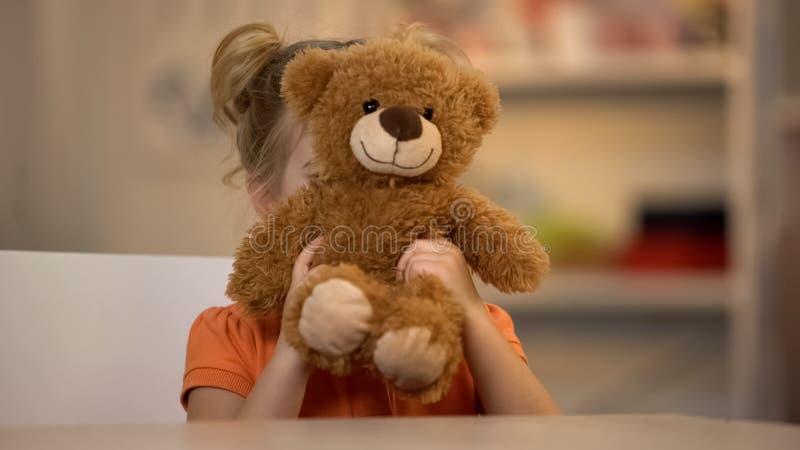 Aanbiddelijk glimlachend meisje die bruine teddybeer, blij jong geitje, gelukkige kinderjaren houden royalty-vrije stock foto