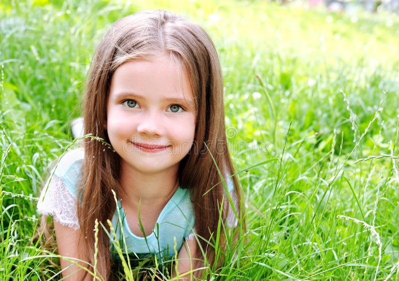 Aanbiddelijk glimlachend meisje die op gras in de zomerdag liggen royalty-vrije stock foto