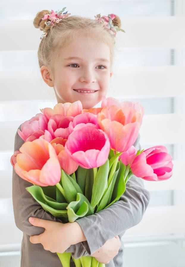 Aanbiddelijk glimlachend meisje met tulpen royalty-vrije stock foto's