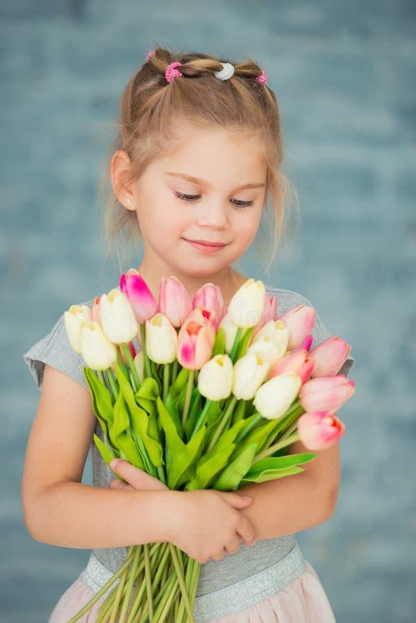 Aanbiddelijk glimlachend meisje met tulpen door het venster stock foto