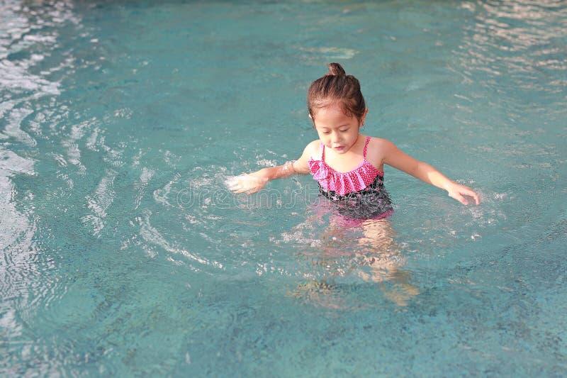 Aanbiddelijk heeft weinig Aziatisch kindmeisje pret het spelen in de pool royalty-vrije stock afbeeldingen
