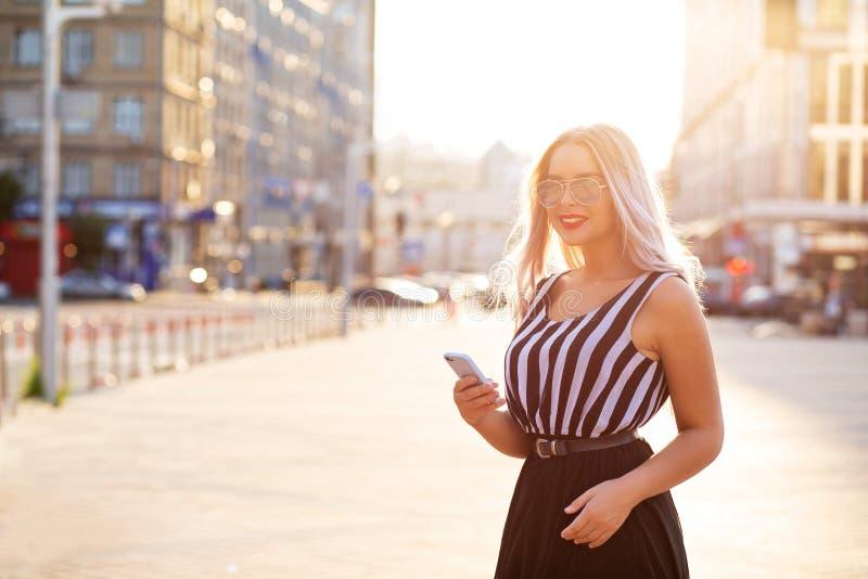 Aanbiddelijk het glimlachen de telefoon van de blonde modelholding mobiel het typen bericht Ruimte voor tekst stock afbeelding