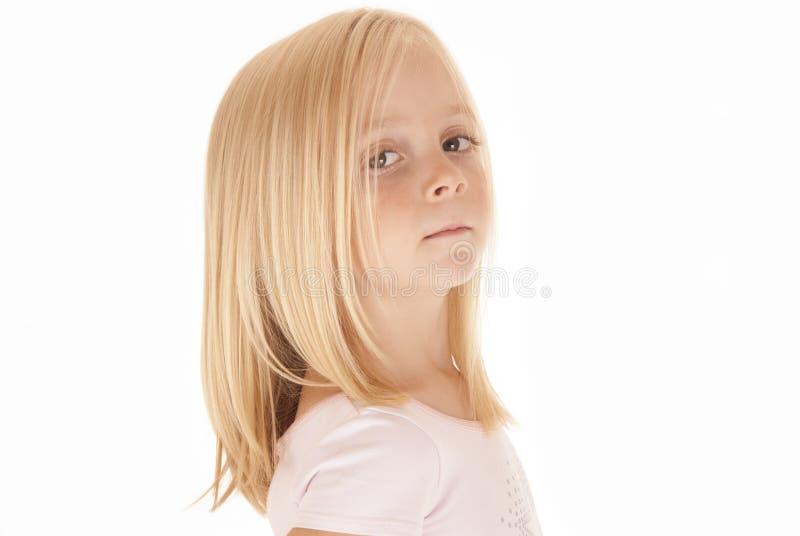 Aanbiddelijk jong blondemeisje in roze hoogste het kijken bedelaars stock fotografie