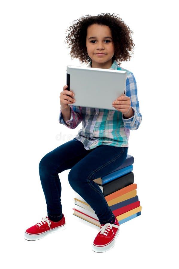 Aanbiddelijk jong geitje met de zitting van tabletpc op boeken royalty-vrije stock foto's