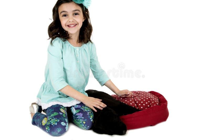Aanbiddelijk jong meisje die de zwarte hond van het laboratoriumpuppy petting stock foto's