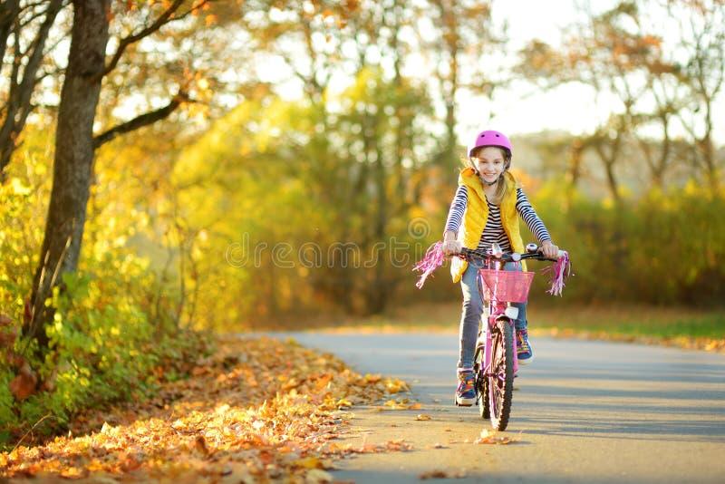 Aanbiddelijk jong meisje die een fiets in een stadspark berijden op zonnige de herfstdag Actieve familievrije tijd met jonge geit royalty-vrije stock foto's