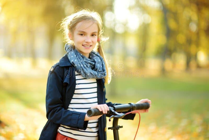 Aanbiddelijk jong meisje die haar autoped in een stadspark berijden op zonnige de herfstavond Preteen vrij kind die een rol berij stock foto