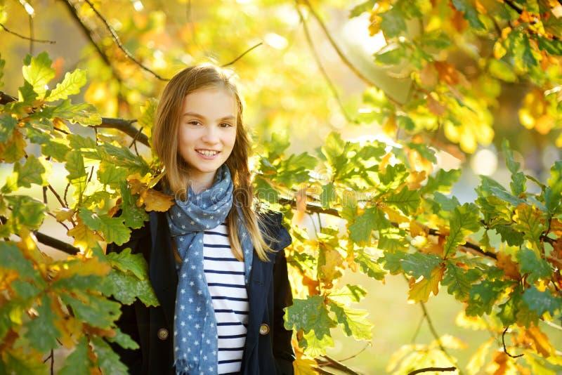 Aanbiddelijk jong meisje die pret op mooie de herfstdag hebben Het gelukkige kind spelen in de herfstpark Jong geitje die geel da stock afbeelding