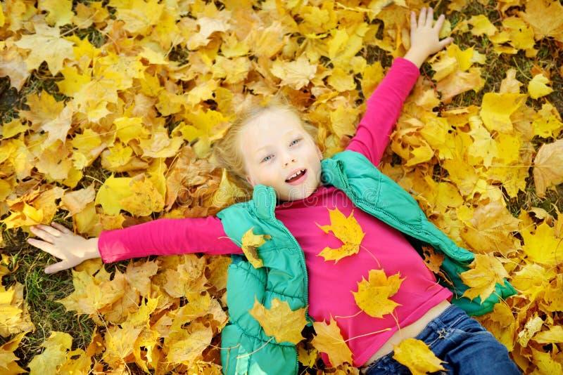 Aanbiddelijk jong meisje die pret op mooie de herfstdag hebben Het gelukkige kind spelen in de herfstpark Jong geitje die geel da royalty-vrije stock fotografie