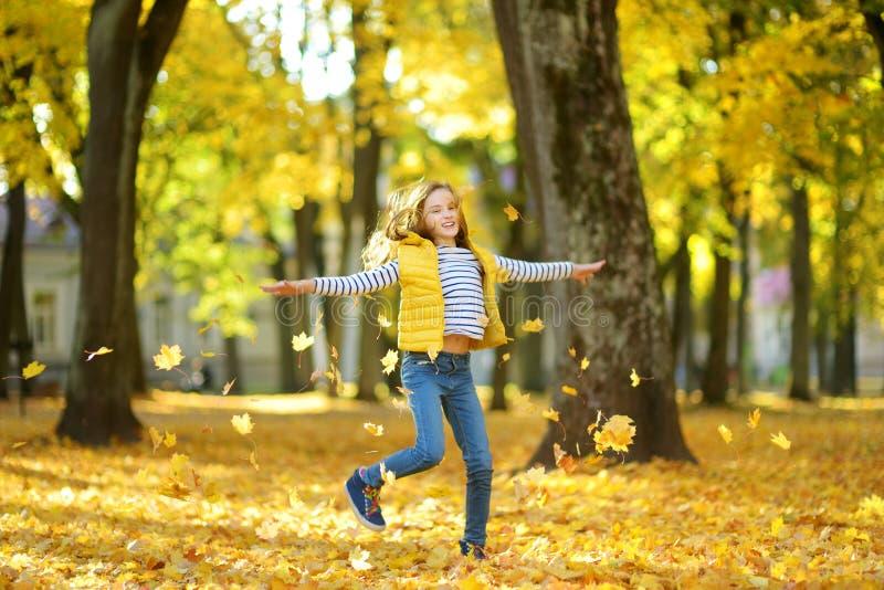 Aanbiddelijk jong meisje die pret op mooie de herfstdag hebben Het gelukkige kind spelen in de herfstpark Jong geitje die geel da stock fotografie