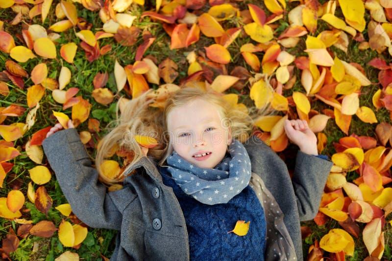 Aanbiddelijk jong meisje die pret op mooie de herfstdag hebben Het gelukkige kind spelen in de herfstpark Jong geitje die geel da stock foto
