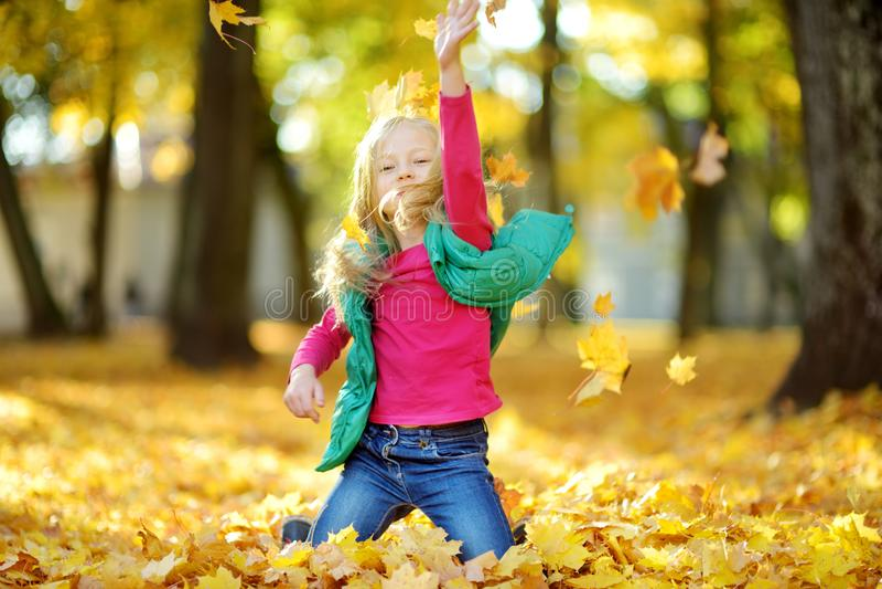 Aanbiddelijk jong meisje die pret op mooie de herfstdag hebben Het gelukkige kind spelen in de herfstpark Jong geitje die geel da royalty-vrije stock afbeelding