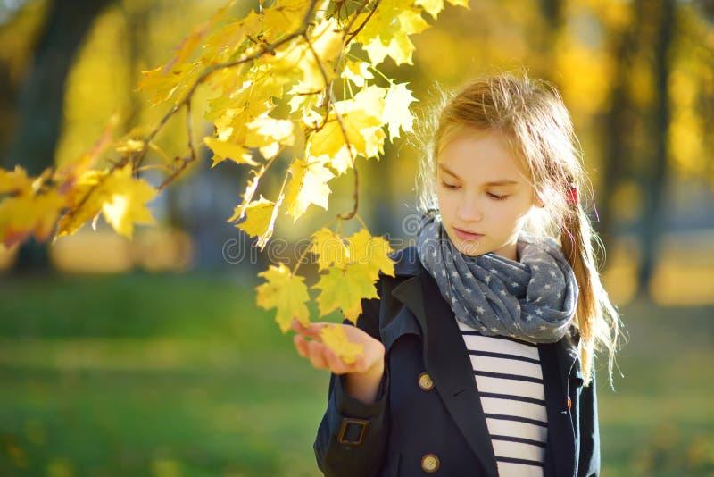 Aanbiddelijk jong meisje die pret op mooie de herfstdag hebben Het gelukkige kind spelen in de herfstpark Jong geitje die geel da royalty-vrije stock afbeeldingen