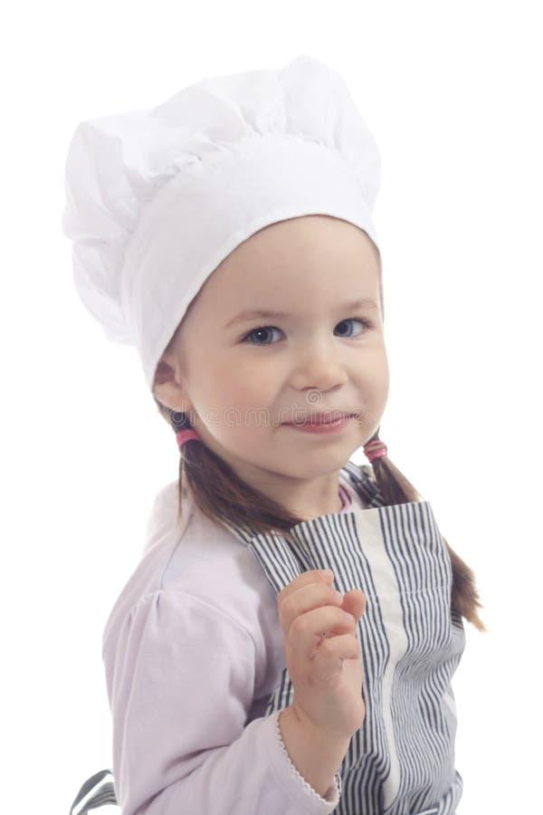 Aanbiddelijk jong meisje in het kokkostuum royalty-vrije stock afbeelding