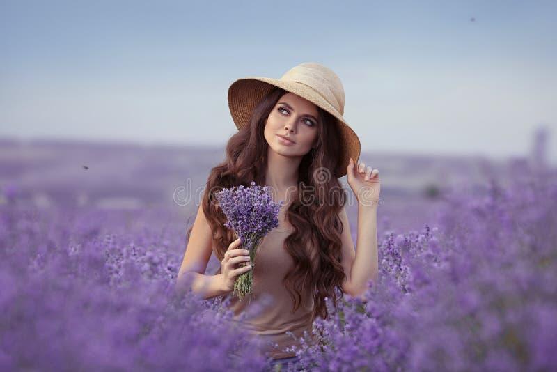 Aanbiddelijk jong vrouwenportret in strohoed over purpere lavendel stock fotografie