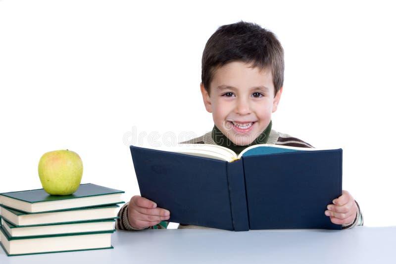 Aanbiddelijk kind dat met boeken en appel bestudeert royalty-vrije stock fotografie