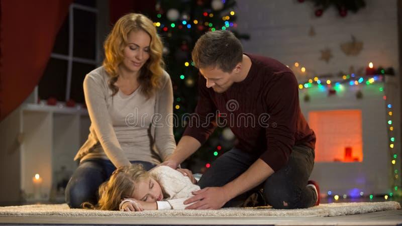 Aanbiddelijk kind gevallen in slaap onder Kerstmisboom, gelukkige ouders die zitten naast stock afbeeldingen