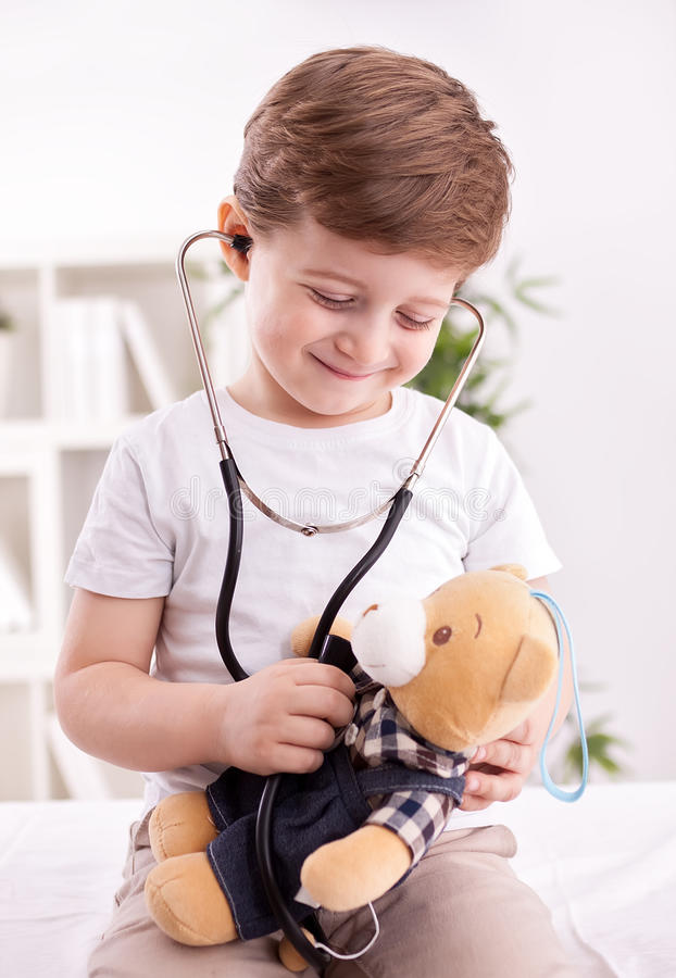 Aanbiddelijk kind met stethoscoop van arts die teddybeer onderzoeken stock afbeelding
