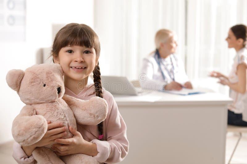 Aanbiddelijk kind met stuk speelgoed en moeder bezoekende arts stock afbeelding
