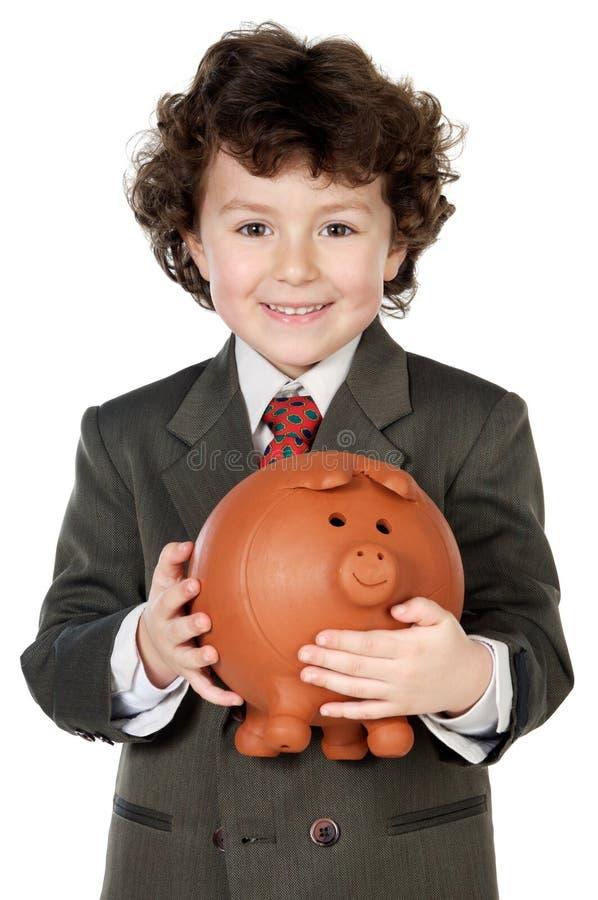 Aanbiddelijk kind met zijn besparingen in zijn spaarpot van piggy royalty-vrije stock foto