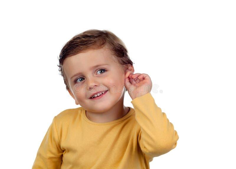 Aanbiddelijk klein kind twee jaar oud wat betreft zijn oor royalty-vrije stock afbeeldingen