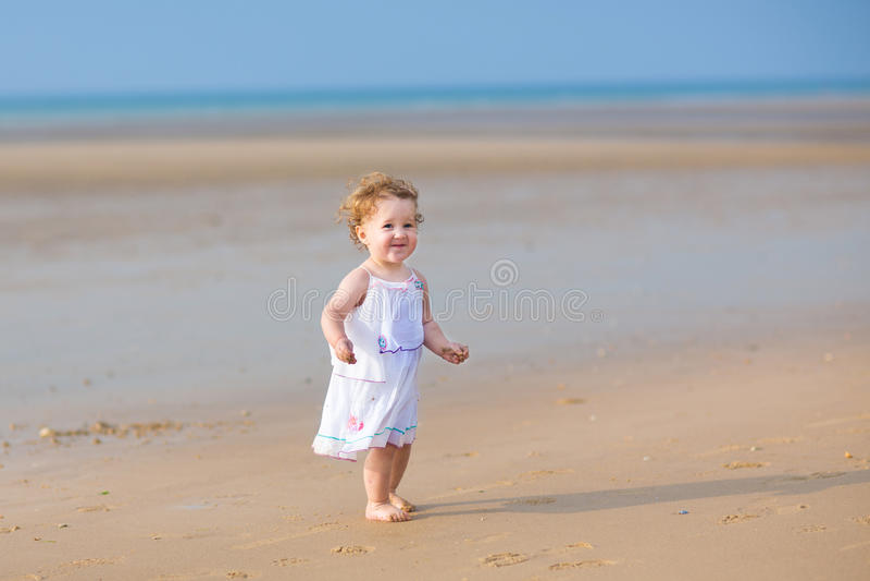 Aanbiddelijk krullend babymeisje die op strand lopen stock foto