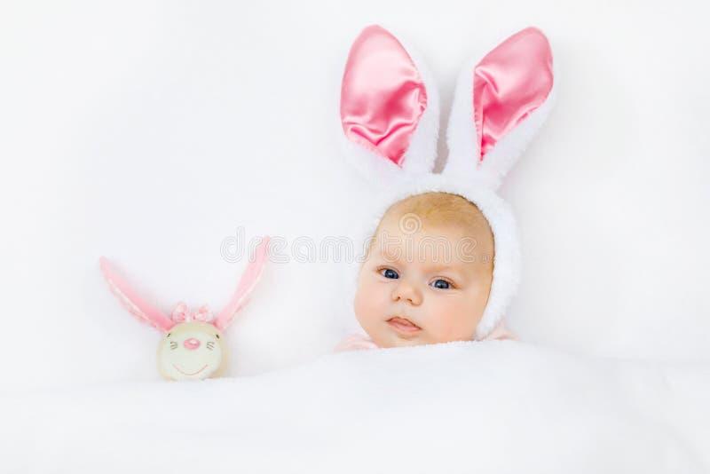 Aanbiddelijk leuk pasgeboren babymeisje in Paashaaskostuum en oren Het mooie kind spelen met het stuk speelgoed van het pluchekon royalty-vrije stock fotografie