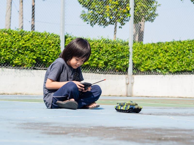 Aanbiddelijk leuk weinig kind die met stuk speelgoed tank spelen, stock afbeeldingen
