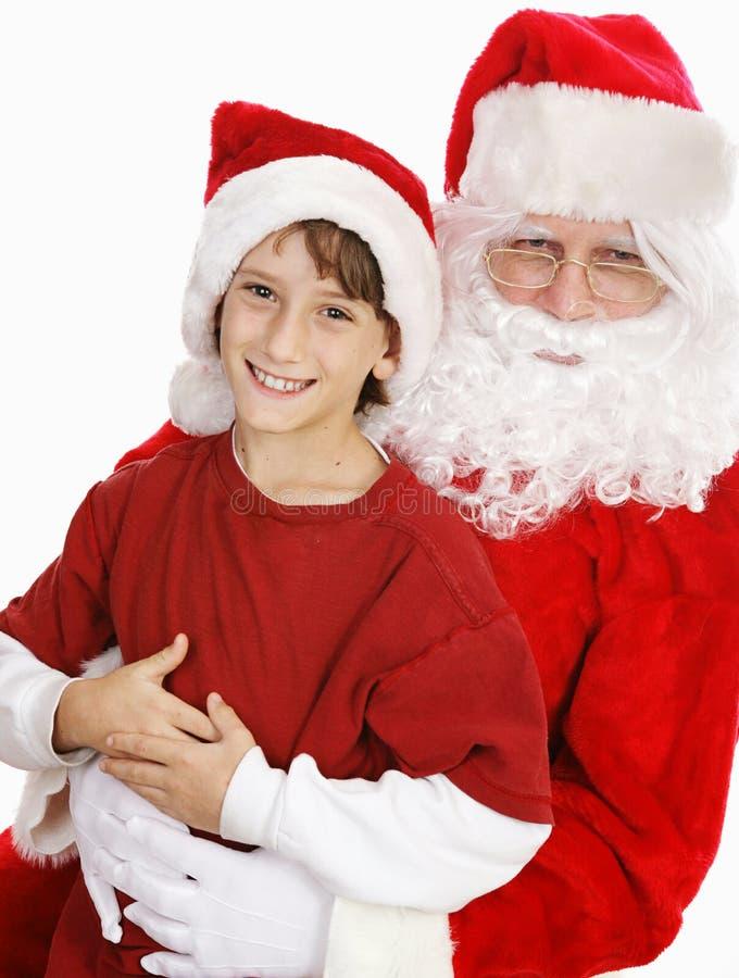 Aanbiddelijk Little Boy op Overlapping Santas stock afbeeldingen