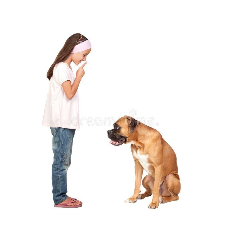 Aanbiddelijk meisje dat tot stilte opdracht geeft zijn hond royalty-vrije stock afbeeldingen
