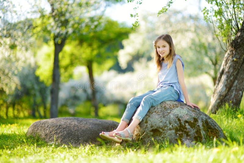 Aanbiddelijk meisje in de bloeiende tuin van de appelboom op mooie de lentedag stock fotografie