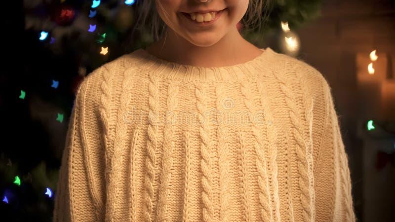 Aanbiddelijk meisje die bij camera glimlachen, die zich op feestelijke verlichte achtergrond bevinden stock foto