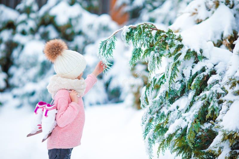 Aanbiddelijk meisje die in de warme dag van de de wintersneeuw gaan in openlucht schaatsen stock foto
