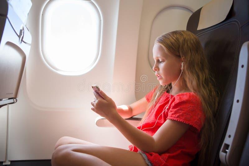 Aanbiddelijk meisje die door een vliegtuig reizen Jong geitje het luisteren muziekzitting dichtbij vliegtuigenvenster stock foto's